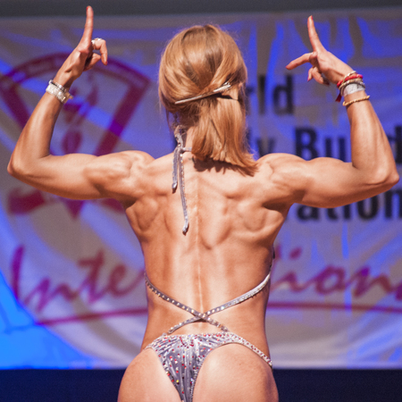 MAASTRICHT, THE NETHERLANDS - OCTOBER 25, 2015: Female fitness model flexes her muscles and shows her best physique in a back doiuble biceps pose on stage at the World Grandprix Bodybuilding and Fitness of the WBBF-WFF on October 25, 2015 at the MECC Thea