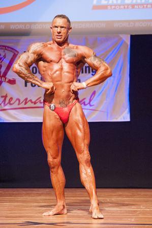 lats: MAASTRICHT, THE NETHERLANDS - OCTOBER 25, 2015: Male bodybuilder flexes his muscles and shows his best physique in a lats spread pose on stage at the World Grandprix Bodybuilding and Fitness of the WBBF-WFF on October 25, 2015 at the MECC Theatre in Maast Editorial