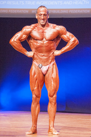 lats: MAASTRICHT, THE NETHERLANDS - OCTOBER 25, 2015: Male bodybuilder Paulo Alexandre Francisco flexes his muscles and shows his best lats spread pose at the World Grandprix Bodybuilding and Fitness of the WBBF-WFF on October 25, 2015 at the MECC Theatre in Ma Editorial