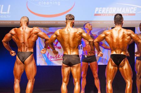 flex: MAASTRICHT, THE NETHERLANDS - OCTOBER 25, 2015: Male bodybuilders flex their muscles and show their best back pose at the World Grandprix Bodybuilding and Fitness of the WBBF-WFF on October 25, 2015 at the MECC Theatre in Maastricht, the Netherlands.