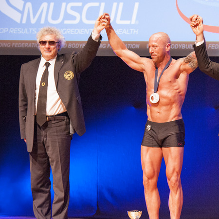 MAASTRICHT, NEDERLAND - 25 oktober 2015: Man bodybuilders Erik Stobbe vieren hun overwinning met ambtenaren op het podium van de World Grandprix Bodybuilding en Fitness van de WBBF-WFF op 25 oktober 2015 in het MECC Theater in Maastricht, de Nether