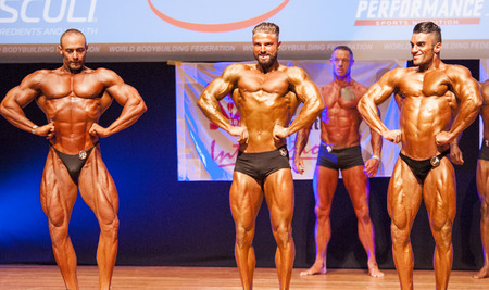 flex: MAASTRICHT, THE NETHERLANDS - OCTOBER 25, 2015: Male bodybuilders flex their muscles and show their best lats spread pose at the World Grandprix Bodybuilding and Fitness of the WBBF-WFF on October 25, 2015 at the MECC Theatre in Maastricht, the Netherland Editorial