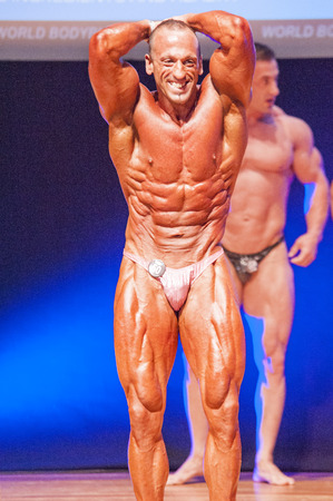 thea: MAASTRICHT, THE NETHERLANDS - OCTOBER 25, 2015: Male bodybuilder Paulo Alexandre Francisco flexes his muscles and shows his best abdominal and thighs pose at the World Grandprix Bodybuilding and Fitness of the WBBF-WFF on October 25, 2015 at the MECC Thea