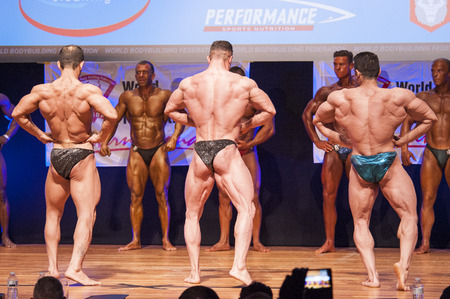lats: MAASTRICHT, THE NETHERLANDS - OCTOBER 25, 2015: Male bodybuilders flex their muscles and shows their best lats spread pose on stage at the World Grandprix Bodybuilding and Fitness of the WBBF-WFF on October 25, 2015 at the MECC Theatre in Maastricht, the  Editorial