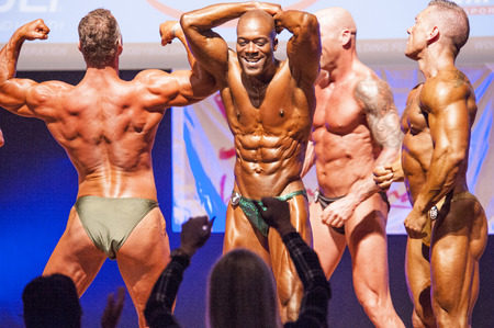 physique: MAASTRICHT, THE NETHERLANDS - OCTOBER 25, 2015: Male bodybuilders flex their muscles and show their best physique on stage at the World Grandprix Bodybuilding and Fitness of the WBBF-WFF on October 25, 2015 at the MECC Theatre in Maastricht, the Netherlan