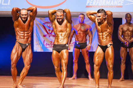 flex: MAASTRICHT, THE NETHERLANDS - OCTOBER 25, 2015: Male bodybuilders flex their muscles and show their best abdominal and thighs pose at the World Grandprix Bodybuilding and Fitness of the WBBF-WFF on October 25, 2015 at the MECC Theatre in Maastricht, the N