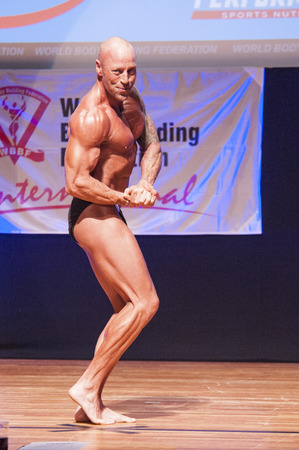 physique: MAASTRICHT, THE NETHERLANDS - OCTOBER 25, 2015: Male bodybuilder Erik Stobbe flexes his muscles and shows his best physique in a chest pose on stage at the World Grandprix Bodybuilding and Fitness of the WBBF-WFF on October 25, 2015 at the MECC Theatre in