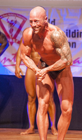 physique: MAASTRICHT, THE NETHERLANDS - OCTOBER 25, 2015: Male bodybuilder Erik Stobbe flexes his muscles and shows his best physique in a most muscular pose on stage at the World Grandprix Bodybuilding and Fitness of the WBBF-WFF on October 25, 2015 at the MECC Th