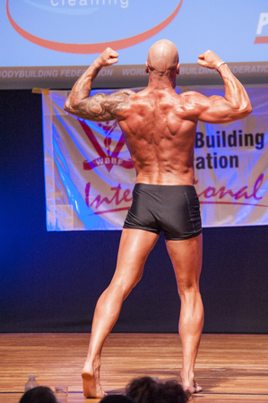 MAASTRICHT, THE NETHERLANDS - OCTOBER 25, 2015: Male bodybuilder Erik Stobbe shows his best back double biceps pose at the World Grandprix Bodybuilding and Fitness of the WBBF-WFF on October 25, 2015 at the MECC Theatre in Maastricht, the Netherlands. Editorial