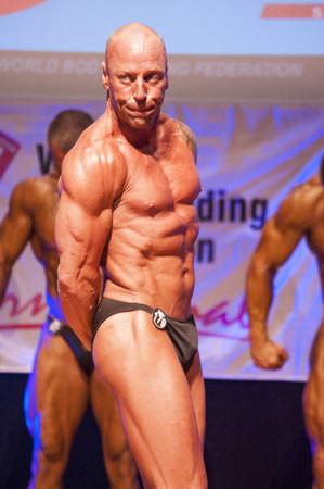 MAASTRICHT, THE NETHERLANDS - OCTOBER 25, 2015: Male bodybuilder Erik Stobbe flexes his muscles and shows his best physique in a triceps pose on stage at the World Grandprix Bodybuilding and Fitness of the WBBF-WFF on October 25, 2015 at the MECC Theatre