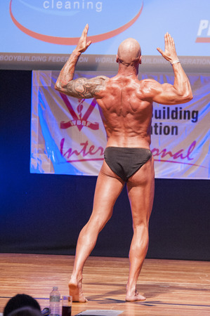MAASTRICHT, THE NETHERLANDS - OCTOBER 25, 2015: Male bodybuilder Erik Stobbe flexes his muscles and shows his best physique in a back double biceps pose on stage at the World Grandprix Bodybuilding and Fitness of the WBBF-WFF on October 25, 2015 at the ME