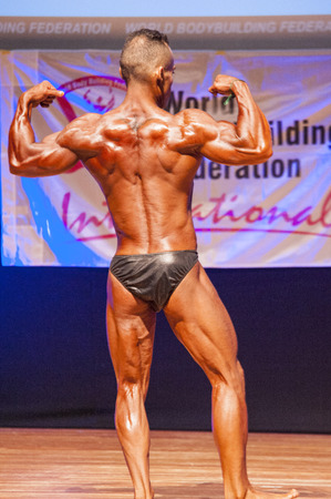 MAASTRICHT, THE NETHERLANDS - OCTOBER 25, 2015: Male bodybuilder flexes his muscles and shows his best back double biceps pose at the World Grandprix Bodybuilding and Fitness of the WBBF-WFF on October 25, 2015 at the MECC Theatre in Maastricht, the Nethe Editorial