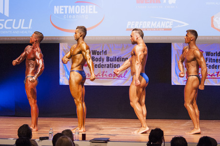 MAASTRICHT, THE NETHERLANDS - OCTOBER 25, 2015: Male bodybuilders flex their muscles and show their best physique in a side pose on stage at the World Grandprix Bodybuilding and Fitness of the WBBF-WFF on October 25, 2015 at the MECC Theatre in Maastricht