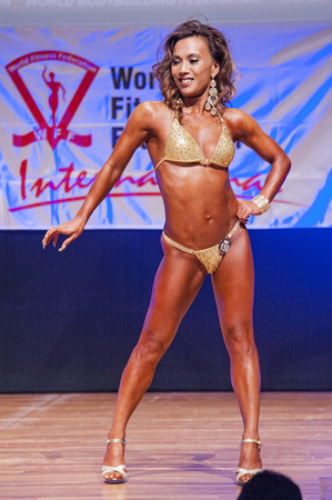 MAASTRICHT, THE NETHERLANDS - OCTOBER 25, 2015: Female physique model Esther Blom shows her best front pose at championship on stage at the World Grandprix Bodybuilding and Fitness of the WBBF-WFF on October 25, 2015 at the MECC Theatre in Maastricht, the