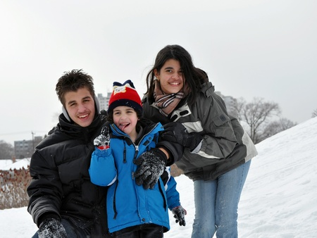 winter: Three siblings enjoy a winter day in a city park