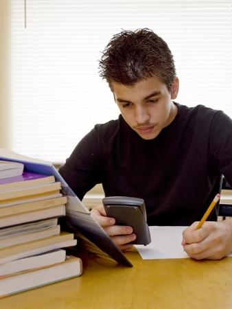 A teenager boys applies himself to study