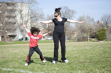A mom and son exercise outdoors photo