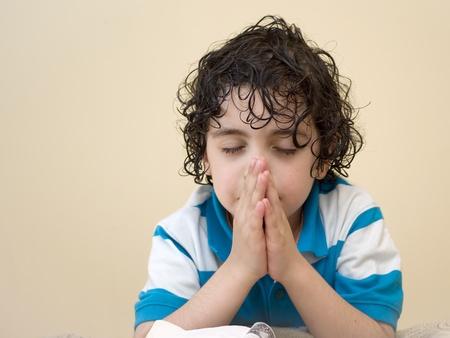 A young boys prays to his creator in heaven. Religious Concept. Foto de archivo