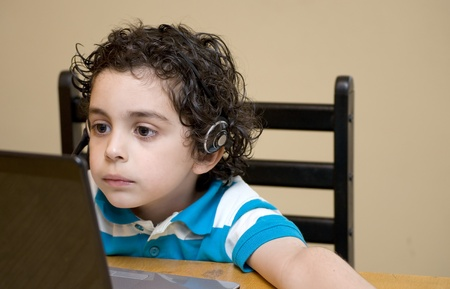 A Young Boy Uses a Laptop to Play Educational Games Online