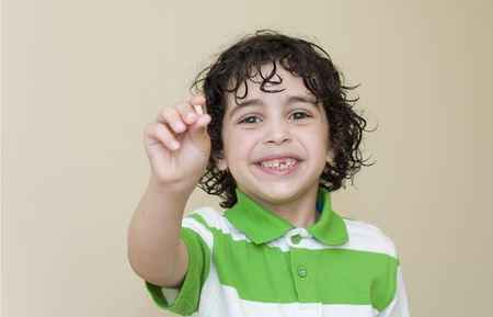 A boy proudly shows his first lost milk tooth photo