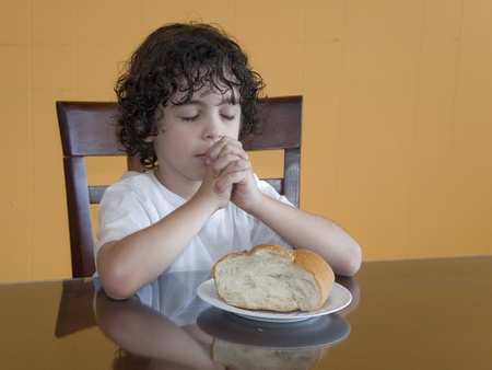 A boys prays to his creator thanking for the daily food