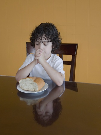 thankfulness: A boys prays to his creator thanking for the daily food