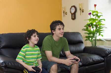 Two brothers play an electronic game at home photo