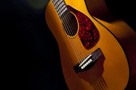 A guitar is display in between a combination of light and shadows