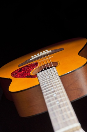 A guitar is display in between a combination of light and shadows photo