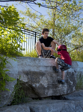 An elder brother helps the smaller climb a rock wall photo