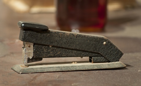office stapler: A view of a vintage stapler sitting on a desk