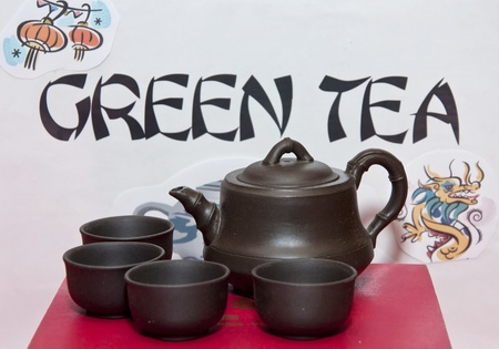 destined: Ancient metal cups and pot destined to serving tea in Asian countries. Green Tea sign