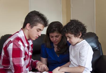 family praying: Familia latina joven con sus manos unidas en un círculo y la cabeza inclinada en oración.
