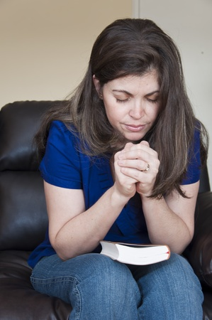 Casual Latin young woman sitting on a couch with her bible on her knees and her hands clasped in prayer.