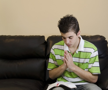 Teenager reading and praying in a Christian fashion to honor God Stock Photo