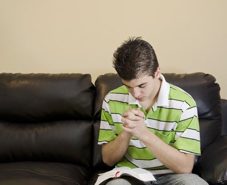 Teenager reading and praying in a Christian fashion to honor God Foto de archivo