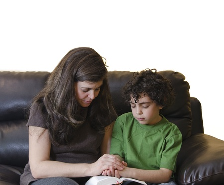 A single mother and her son praying to God in their daily devotional