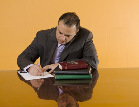 Religious man writing in his office with the Bible in front Stock Photo - 13296912