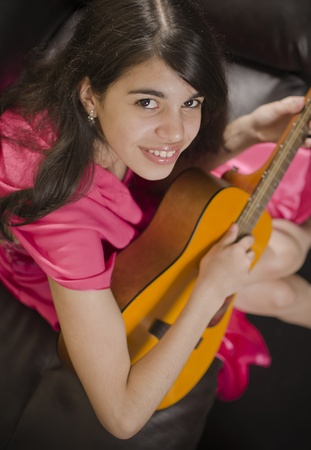 Hispanic girl enoying herself while playing the guitar at home. photo