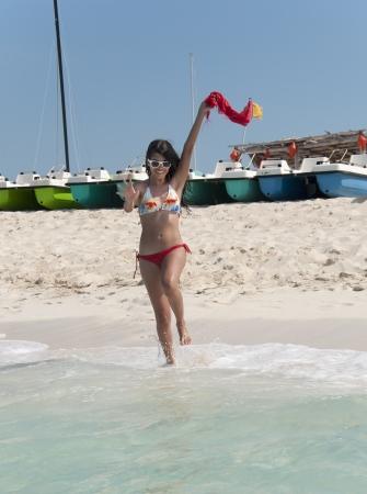 cuba girl: Latin teenager girl running and enjoying a tropical blue water beach in Cuba