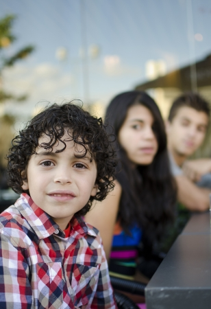 Three Hispanic children waiting for dinner in a restaurants patio in Toronto photo