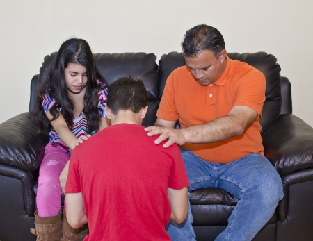 family praying: Christian devotional time where a family prays for each other