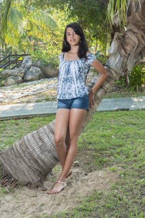 fifteen: Hispanic girl leaning to a coconut tree Stock Photo