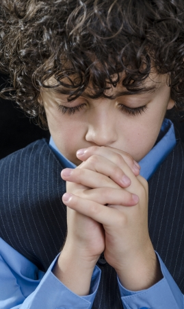 Young Latin boy praying and praising God photo