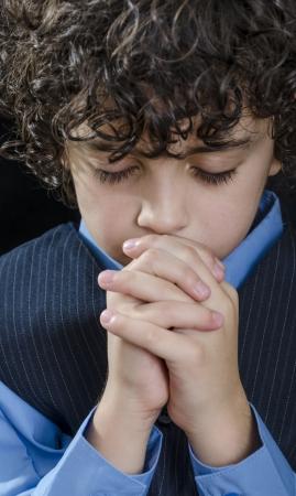 Young Latin boy praying and praising God Stock Photo