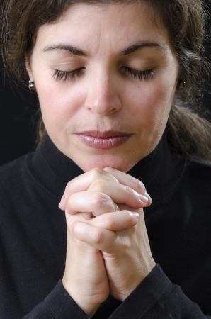 Hispanic woman praying and praising the Lord