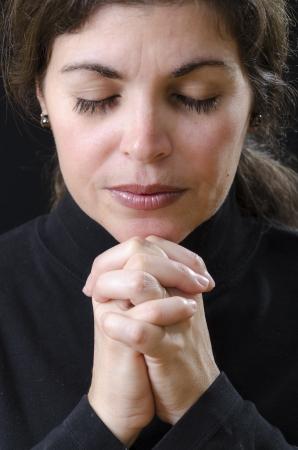 Hispanic woman praying and praising the Lord