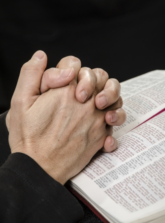 Hands clasped over a Bible in reverent prayer photo