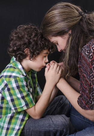 praying together: Mother and son praying and praising God