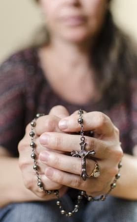 Catholic woman praying with a Rosary photo